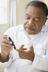 African man using diabetes testing strip