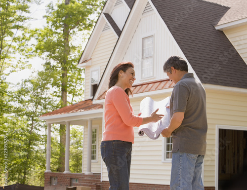 Hispanic couple viewing blueprints for home addition