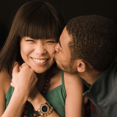 African man kissing Asian girlfriend