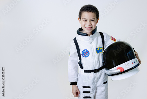 Mixed race boy in astronaut costume