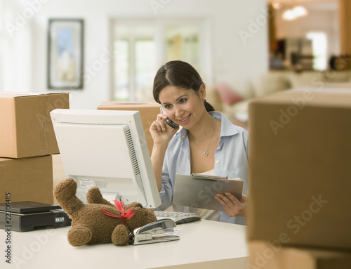Female business owner surrounded by cardboard boxes