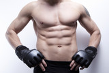 Male's torso. Young man in gym, with boxing training gloves