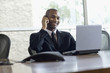 African businessman with laptop talking on cell phone