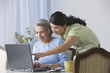 Hispanic woman showing senior mother how to use laptop