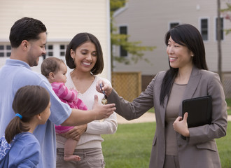 Hispanic family receiving keys to house from realtor