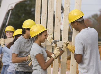 Volunteers wearing hard-hats working at construction site