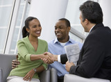 African couple shaking hands with financial advisor