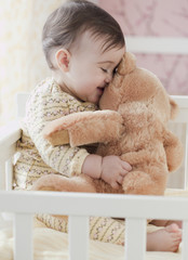 Mixed race baby girl snuggling teddy bear