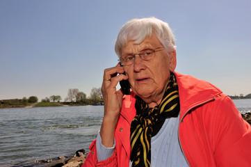 Alte Dame mit Handy am Flussufer