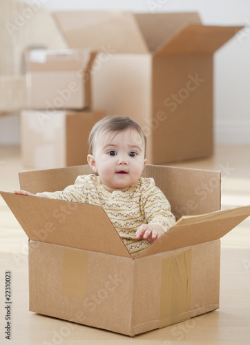 Mixed race baby girl sitting in cardboard box