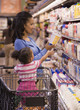 Mixed race woman shopping with daughter in grocery store