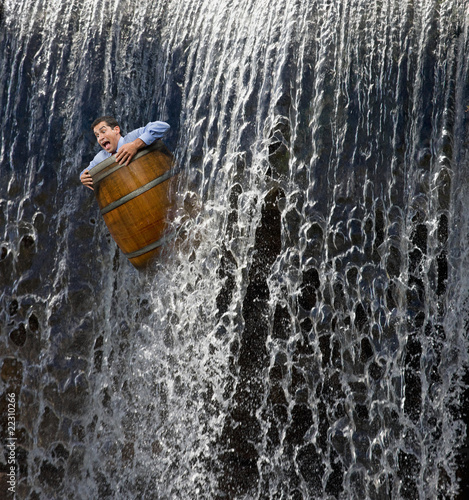 Businessman going over waterfall in barrel