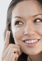 Mixed race woman applying cream under eyes