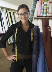 Mixed race clothing designer holding fabric