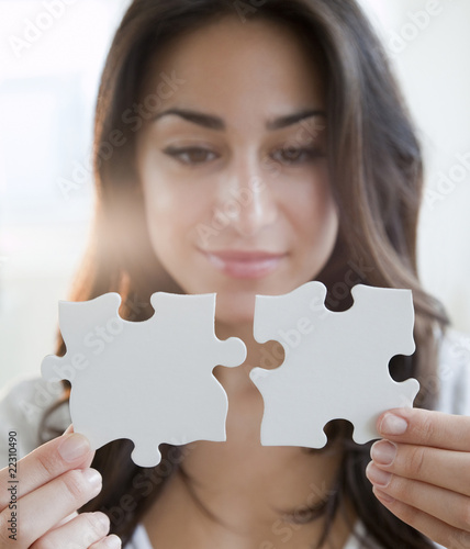 Hispanic woman holding two puzzle pieces