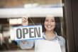 Hispanic woman hanging open sign on door
