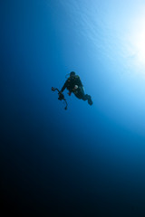 An underwater photographer out in the blue ocean.
