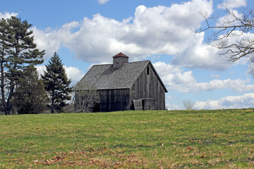 Old barn in field with bright cloudy sky
