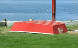 Old plywood red skiff with ocean in the background poster