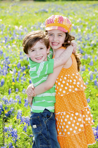 Two Children Hugging in a Field of Flowers