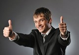 Happy businessman showing his thumbs up with smile .