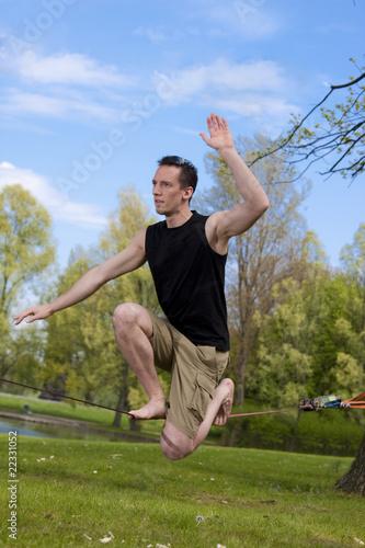 Mann hockt auf Slackline