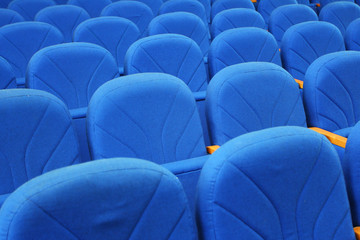 Closeup of blue armchairs backs in conference hall