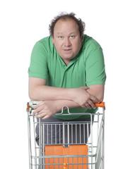 homme en grande surface avec sa charette de magasin