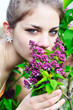 Beautiful teen girl smelling lilac blossoms