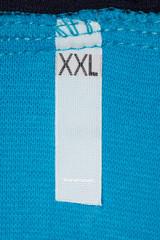 Label size XXL on blue cloth. Large size clothing.