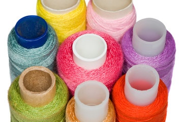 spools with multi-coloured sewing threads isolated on white