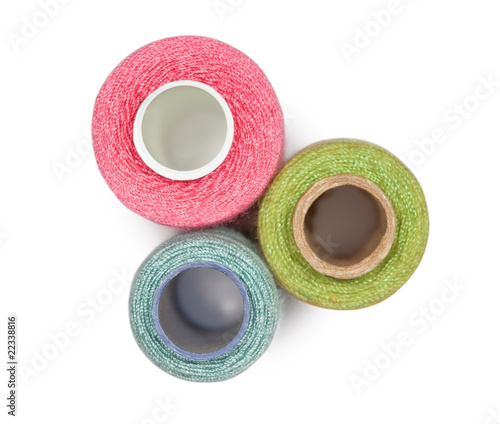 Three coils with multi-coloured sewing threads isolated on white
