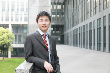 a yong Asiatic businessman  is standing outdoor