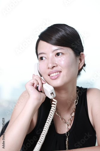 young asian business woman working with telephone