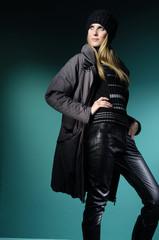 Fashion model in winter dress on blue light studio