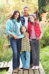 Family Group Standing Outdoors On Wooden Walkway In Autumn Lands