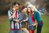 Upset Teenage Girl With Friends Gossiping In Background poster