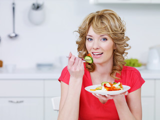 Young woman eating salad in the kitchen