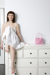flirting woman in white dress sitting on chest of drawers