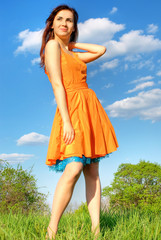 Girl in orange dress against the sky