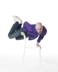 jeune homme en équilibre sur une chaise