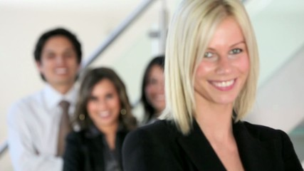 Beautiful business woman smiling with a group behind her