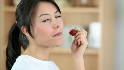 Woman eating an strawberry