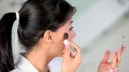 Business woman putting make up