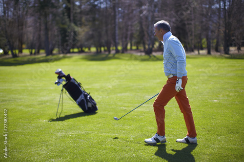 Golfer man with his bag on a green walking
