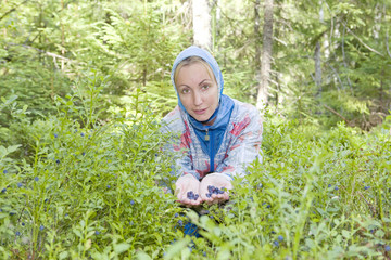 Young woman plucks bilberry in forest