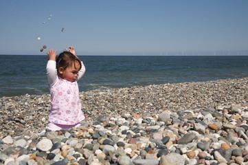 Little girl throwing stones over her head