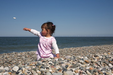 Happy child on the beach throwing rocks