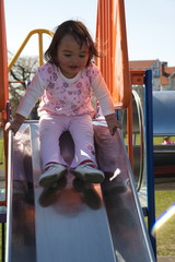 Toddler playing on a park slide