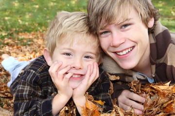 Brother's laying  in a pile of leaves